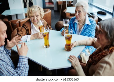 Three elegant-looking senior women listening to their male friend with interest while relaxing in pub with glasses of beer
