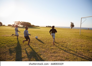 Three elementary school kids playing football in a field