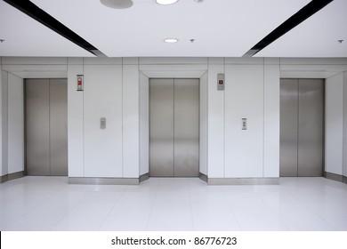 Three elevator doors in office building