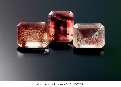 Three emeral cut sunstones sit on a black refective background. The stone are pale red, orange in color and show stronged shilling.
