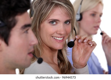three employees holding headsets