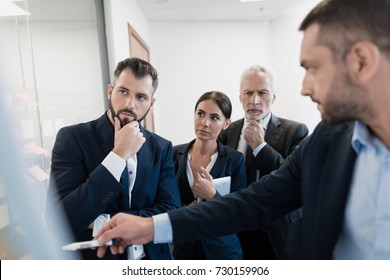 Three employees and their director are next to the rack with the schedule. Leadership concept. They carefully consider it. They are concentrated