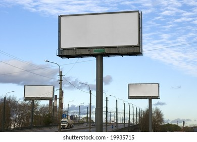 Three empty billboards  along the road.