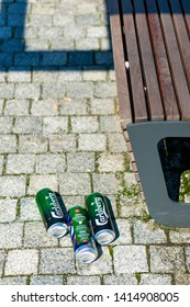 Three empty Carlsberg beer cans laying on the ground next to a wooden park bench on circa June 2019 in Poznan, Poland.