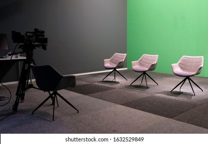 Three empty chairs in a TV studio with green screen