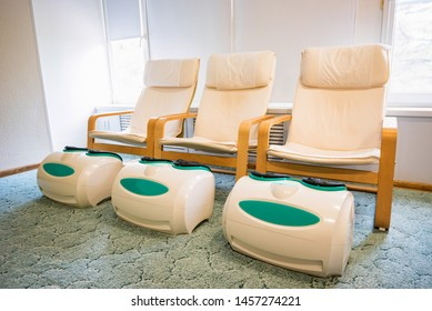 Three empty foot massage chairs in a spa cabinet
