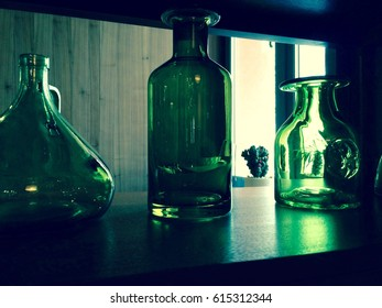 Three empty green glass old bottles stand on a shelf in a row. Example of decorating the interior of the room.