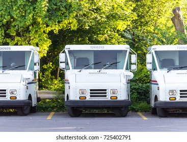 Three Empty, Parked, United States Post Office Trucks Lined up in a Row in a Parking Lot, Exterior, Evening Sunlight, Medium Shot, Eye Level, Trees in Background.