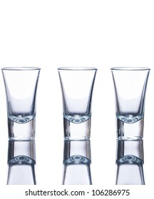 Three empty shot glasses on a reflective surface. Isolated on white.