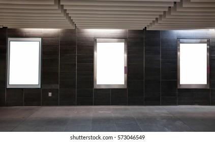 three empty white blank banners billboards in the dark modern urban corridor