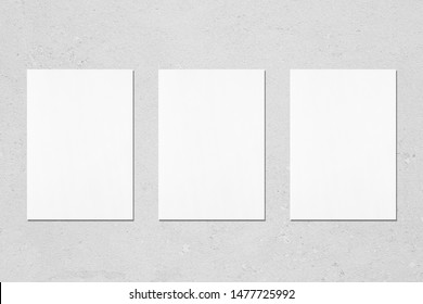Three empty white vertical rectangle poster mockups with soft shadows on neutral light grey concrete wall background. Flat lay, top view