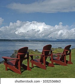 Three empty wooden muskoka style chairs at watch over sea or river channel. Location is looking west from Quadra Island between Vancouver Island and the mainland of British Columbia, Canada