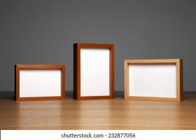 three empty(blank) wood photo frames(teak, cherry, oak) on the wood table(desk) at the studio.