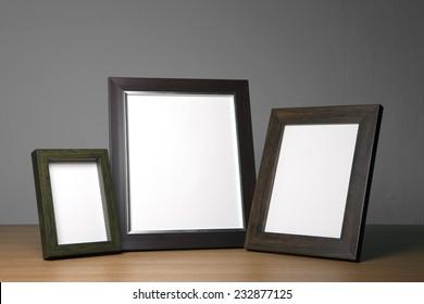 Three empty(blank) wood photo frames(walnut) on the wood table(desk) at the studio.