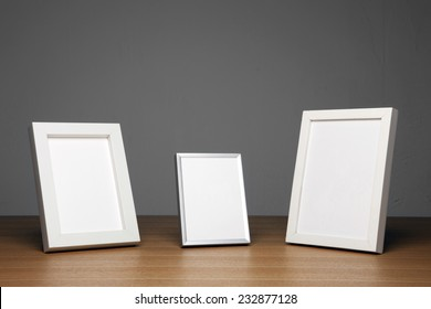 three empty(blank) wood photo frames(white) on the wood table(desk) at the studio.