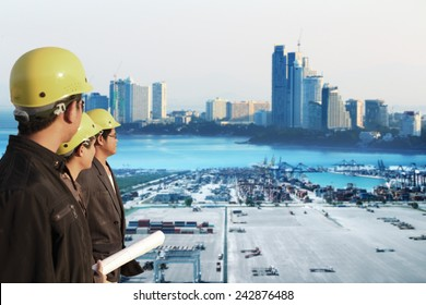 three engineer team standing in front of cranes at the container port terminal with big city background