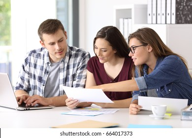 Three entrepreneurs analyzing and commenting reports together sitting in a desk at office