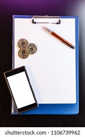 Three Ethereum (ETH) physical golden and shiny coins among with a clipboard with blank paper sheets, a pen and a mobile phone (smartphone) with a trading app. Ethereum is a digital cryptocurrency