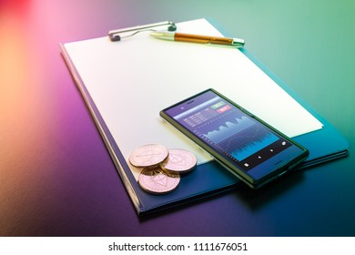 Three Ethereum (ETH) physical golden and shiny coins among with a clipboard with blank paper sheets, a pen and mobile phone (smartphone) with a cryptocurrency trading app. Ethereum is a cryptocurrency