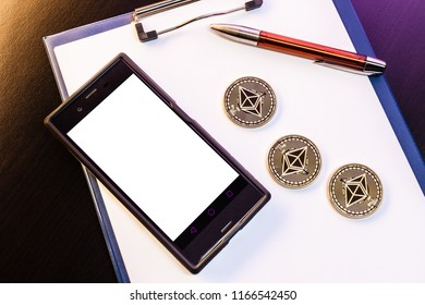 Three Ethereum (ETH) physical golden and shiny coins among with a clipboard with blank paper sheets, a pen and a mobile phone with a cryptocurrency trading app. Ethereum is a digital cryptocurrency