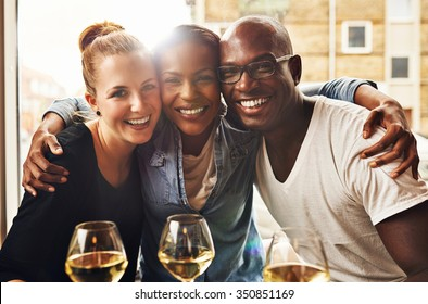 Three ethnic best friends smiling at camera and hugging