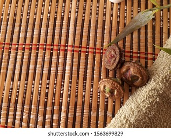 Three eucalyptus seeds on a bamboo mat frame with green towel and eucalyptus leaves. Space copy. Spa concept. Brown eucalyptus seeds closeup. Plant seed. Gumnuts, fruit of the Australian Eucalyptus