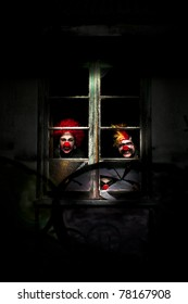 Three Evil Looking Clowns Peering Out The Window Of A Shadowy Building