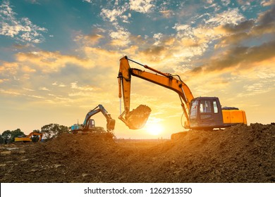 Three excavators work on construction site at sunset
