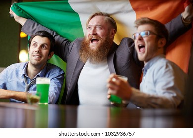 Three excited fans with national irish flag sitting in pub and watching football match