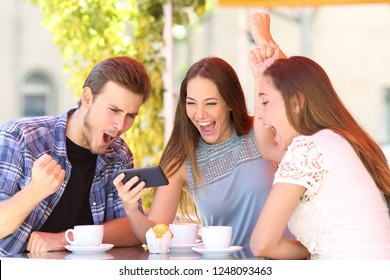 Three excited friends celebrating good news watching smart phone media content in a coffee shop