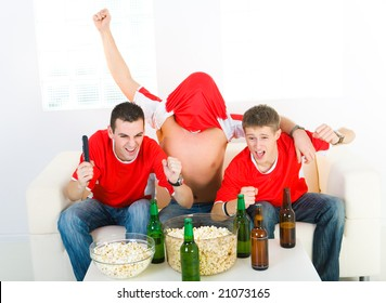 Three exciting men sitting on couch and watching sport on TV. Front view.