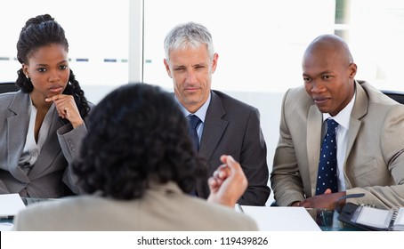 Three executives are earnestly listening to an associate