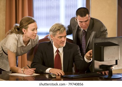 Three executives in the office looking at computer screen.