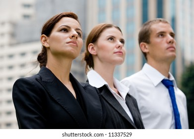 Three executives standing outside with city buildings behind