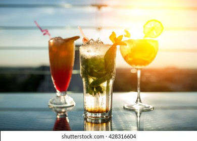 three exotic cocktails in rays of sun; fresh summer cold alcohol drinks;