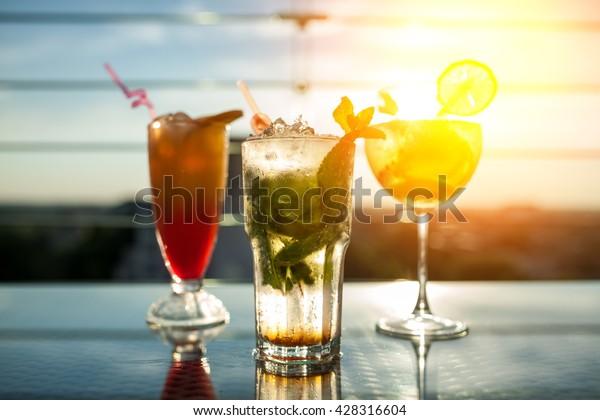 три экзотических коктейля в лучах солнца; свежие летние холодные алкогольные напитки;