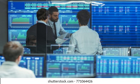 Three Experienced Stock Traders Talking Business. They Work for a Big Stock Exchange Firm. Office is Full of Displays Showing Data, Infographics and Numbers.