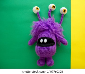 three eye purple monster amigurumi on green and yellow background