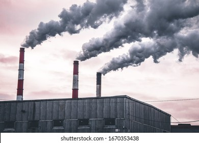 Three factory chimneys emit puffs of smoke. The concept of air pollution, environment, industry and ecology, global warming.