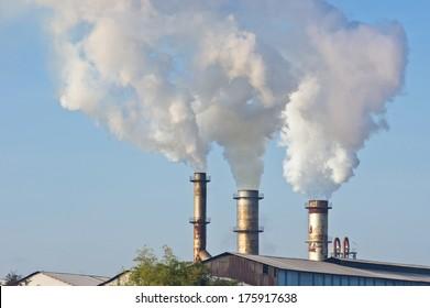 three of factory smokestack against morning sunlight