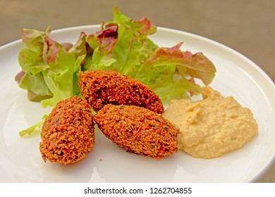 Three falafel balls, houmous and salad on a plate, middle eastern food. selective focus