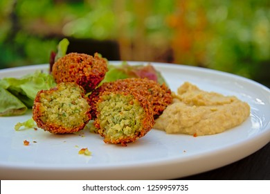 Three falafel balls of which one is cut in half , houmous and salad on a plate, middle eastern food. selective focus