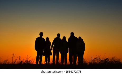 Three families silhouette gathering for a photo at sunset