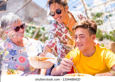 three family people with different ages and generations at lungh on a sunny day outdoor leisure activity, grandmother, mother and son heving fun together. people in happiness with smiles