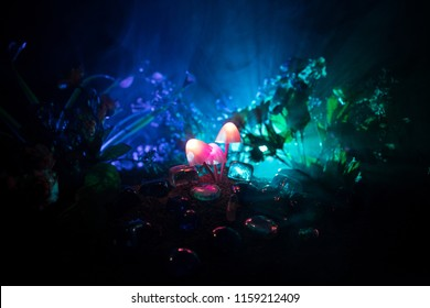 Three fantasy glowing mushrooms in mystery dark forest close-up. Beautiful macro shot of magic mushroom or three souls lost in avatar forest. Fairy lights on background with fog. Selective focus