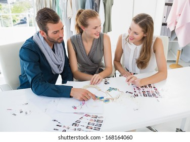 Three fashion designers discussing designs in a studio