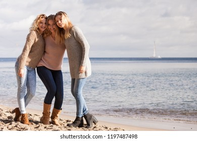Three fashionable women sisters friends wearing sweaters during warm autumnal weather spending their free time on sunny beach. Fashion models outdoor