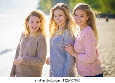 Three fashionable women wearing sweaters during warm autumnal weather spending their free time on sunny beach. Fashion models outdoor
