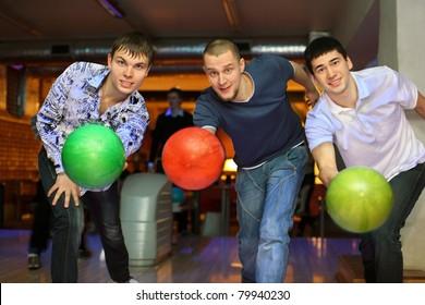 Three fellows throw balls on lane in bowling club