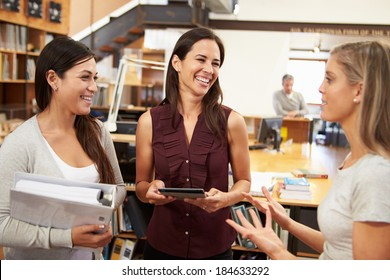 Three Female Architects Chatting In Modern Office Together